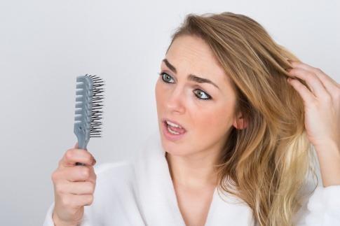 Eine Frau hält eine Bürste mit vielen Haaren darin in der Hand