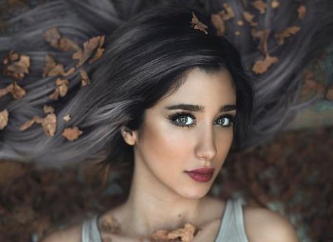 Eine Frau hat graue Strähnen im Haar und versucht es vielleicht zu renaturieren