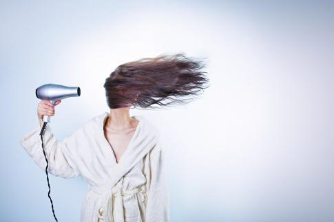 Eine Frau fönt ihre Haare mit einem Fön