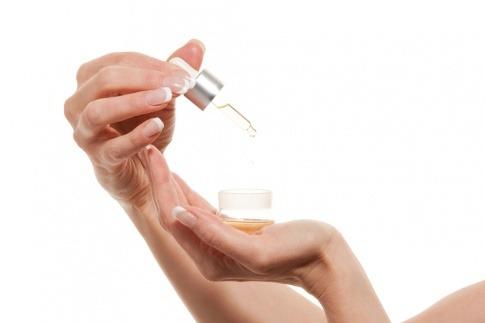 Eine Frau hält Öl für die Haut in den Händen