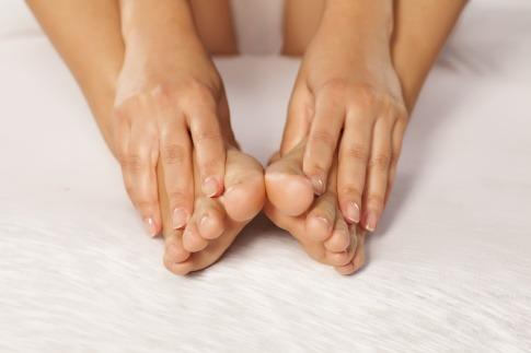 Hände umfassen Beine mit Lymphödem