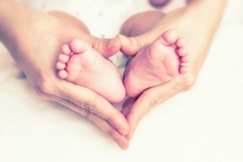 Zwei Hände eines Erwachsenen umfassen zwei Kinderfüße und formen ein Herz