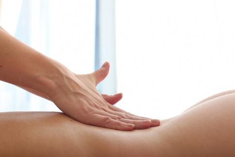 Eine Hand massiert bei einer erotischen Massage einen nackten Rücken