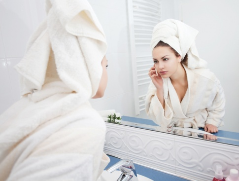 Eine Frau hat ein Handtuch um die Haare gewickelt um sie zu trocknen