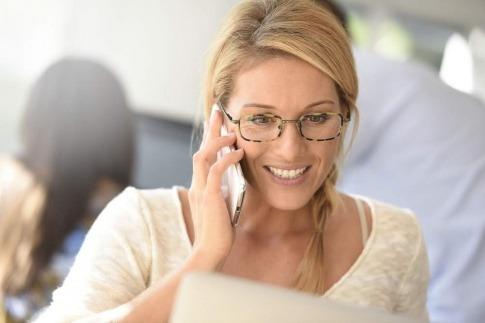 Eine Frau telefoniert mit ihrem Handy und lächelt dabei. Sie macht sich wohl keine Gedanken darüber, ob man Handystrahlung abschirmen sollte.