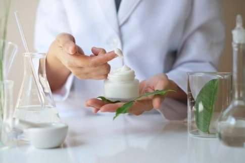 Eine Frau hat Creme auf dem Finger und Hanf im Labor