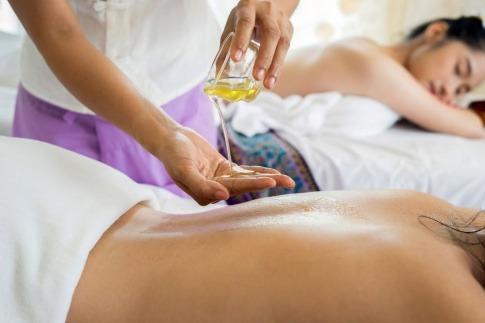 Eine Masseurin tröpfelt ein wenig Hanföl für Massage- und Entspannungszwecke auf ihre Handflächen, bevor sie ihre Kundin massiert.