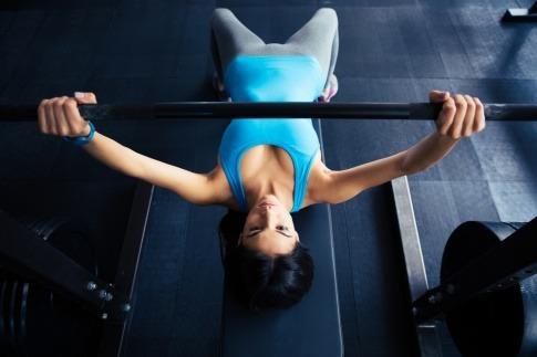 Eine Frau liegt auf einer Bank zum richtig trainieren, zuhause