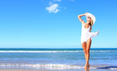 Frau am Strand will Haut auf Sonne vorbereiten