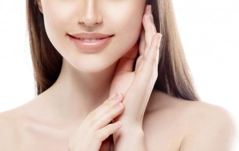 Die untere Gesichtshälfte, Hals und Dekolleté einer braunhaarigen Frau sind auf dem Foto abgebildet. Sie hat schöne Haut und schöne Lippen. Außerdem lächelt sie leicht.
