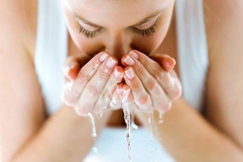 Frau reinigt ihr Gesicht, indem sie es wäscht