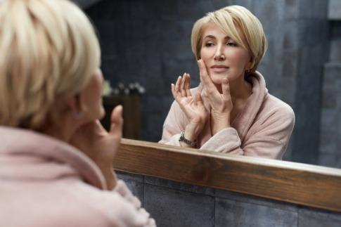 Frau in den Wechseljahren betrachtet Haut vor dem Spiegel