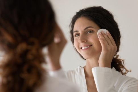 Frau reinigt ihr Gesicht am Abend