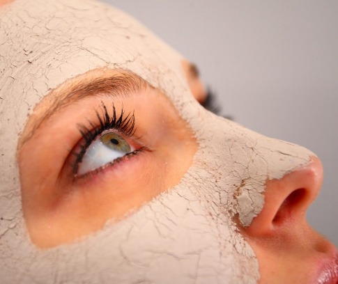 Frau mit Maske aus Heilerde