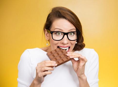 Frau mit Heißhunger beißt in Schokoladentafel