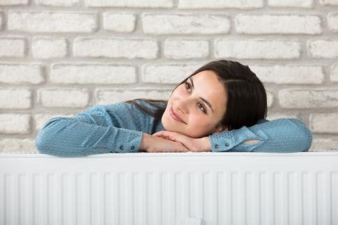 Eine Frau liegt auf einem Heizkörper