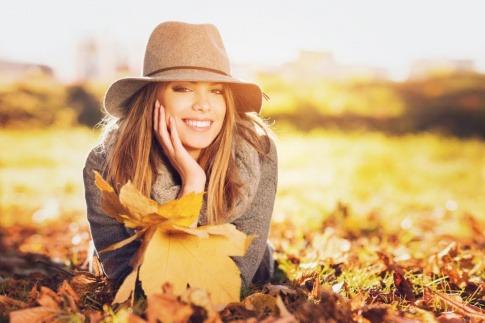 Eine Frau liegt auf einer mit Laub bedeckten Wiese und lächelt in die Kamera. Sie weiß anscheinend sehr genau, wie sie den Herbst genießen kann.