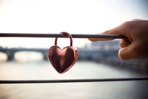 Ein Herz aus Metall hängt auf einem Zaun