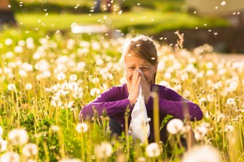 Mädchen mit Heuschnupfen in einem Blumenfeld