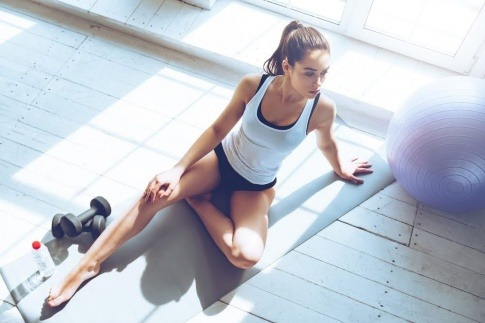 Eine junge Frau in einem Sportoutfit sitzt auf einer Yoga Matte und ruht sich zwischen Intervallen eines HIIT Trainings aus.