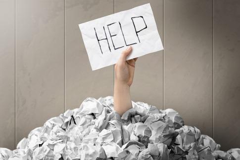 Eine Hand hält ein Schild mit der Aufschrift Help aus einem Berg Papier