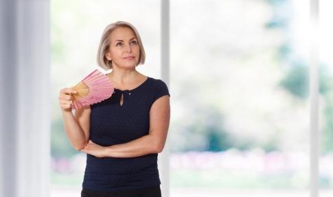 Frau in den Wechseljahren mit Fächer gegen Hitzewallungen