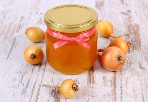 Einige Zwiebeln liegen um ein Honigglas herum