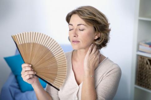 Eine Frau hält einen Fächer wegen der Hitzewallungen durch Hormone (Wechseljahre)