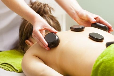 Heiße Steine werden für eine Hot Stone Massage auf dem Rücken verteilt