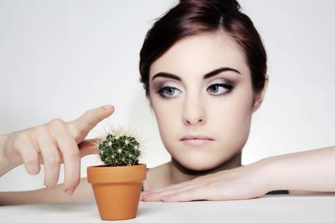 Eine Frau mit hypersensibler Haut greift auf einen Kaktus