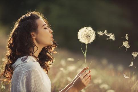 Eine Frau lebt im Moment und genießt das Sein. Sie bläst eine Pusteblume