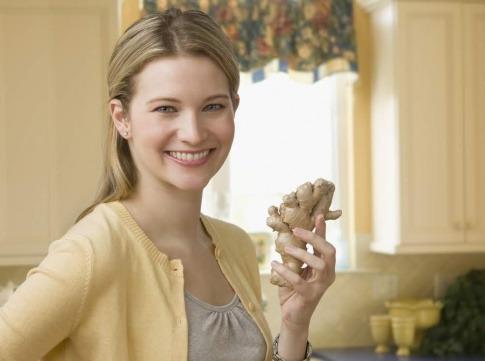 Eine Frau hält eine Knolle Ingwer in den Händen