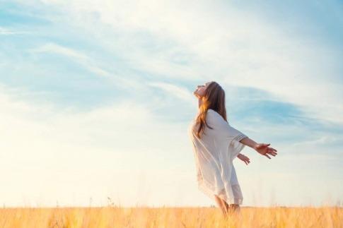 Diese Frau, die mit ausgebreiteten Armen am Strand steht und der Sonne entgegenblickt, hat ihre innere Klarheit offensichtlich bereits erlangt.