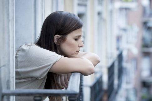 Eine Frau steht am Balkon und wirkt verloren