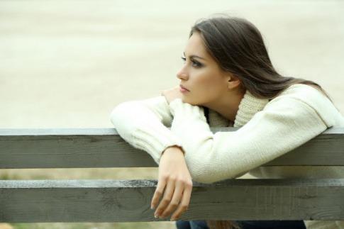 Eine Frau sitzt im Herbst auf einer Parkbank und blickt verloren in die Ferne.