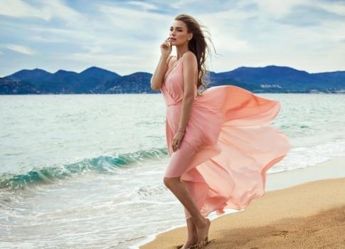 Eine Frau bedeckt ihren Intimbereich mit einem Kleid