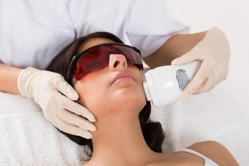 Frau die sich gerade eine Gesichtsbehandlung mit Ultraschall machen lässt