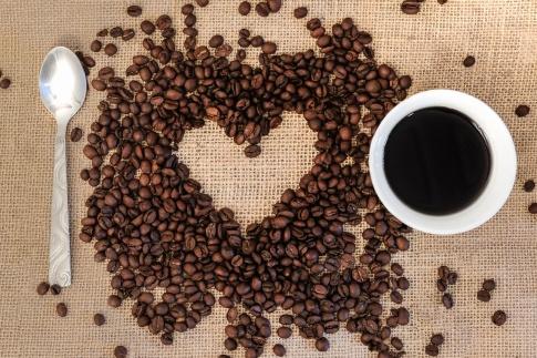 Neben einer Kaffeetasse liegen Kaffeebohnen und ein Löffel