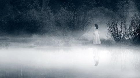 Wer keine Gefühle mehr hat, fühlt sich wie diese Frau an einem nebligen See am Abend.