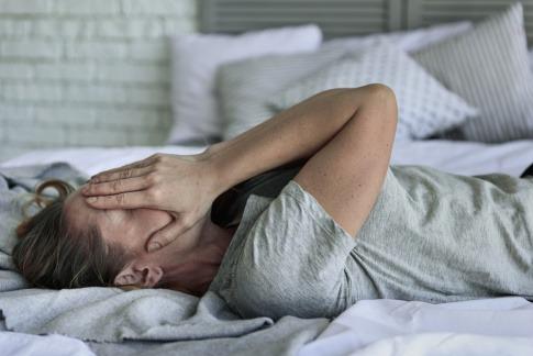 Eine Frau hat keine Hoffnung mehr und liegt am Bett