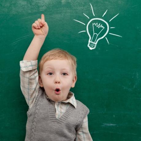 Ein Kind hält den Zeigefinger hoch, auf der Tafel hinter ihm ist eine Glühbirne