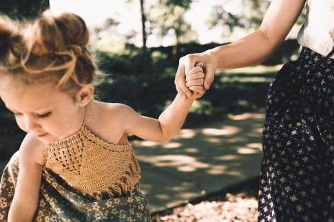 Eine Hand hält ein Kind an der Hand