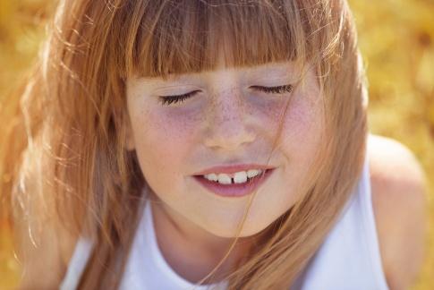 Ein Kind lächelt im Sommer und hat Pigmentflecken