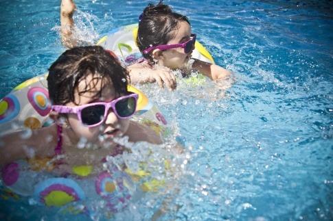 Kinder sind im Schwimmbad und tragen Sonnenschutz