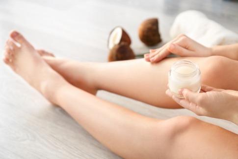 Eine Frau pflegt ihre Haut mit Kokosfett, daneben liegt eine Kokosnuss