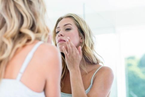 Frau blickt kritisch in den Spiegel und braucht Kollagen als Nahrungsergänzung