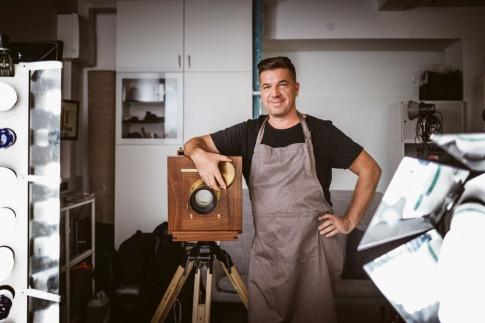 Der Fotograf Erik Diewald steht neben einer Großformatkamera aus Holz