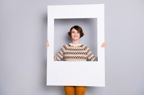 Frau hält Rahmen aus Pappe hoch. Sie möchte ihre Komfortzone verlassen, Tipps finden, die ihr dabei helfen und ein aufregenderes Leben führen.