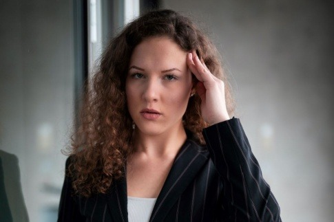 Eine Frau fasst sich an die schmerzenden Schläfen.