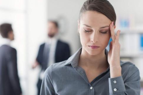 Eine Frau hat Kopfweh nach Mobbing am Arbeitsplatz